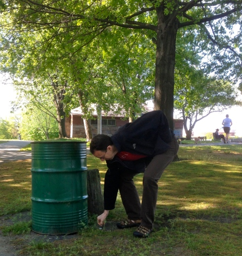 A good citizen picks up trash and deposits it in one of the NEWLY PLACED trash cans in the park.