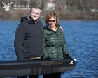 Nikolay Kurmakov's son Andrew and wife Laura pose with the boat dedicated to the longtime Riverside and Simmons Coach.